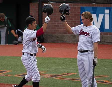 Marc Gallegos of Corban and Portland's Kevin Farley celebrate Marc's homer